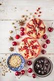 Stillleben mit Granatapfel, Kirsche und Gewürzen auf dem weißen Holztisch Konzept von den orientalischen Früchten vertikal lizenzfreie stockfotos