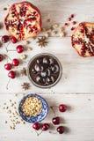 Stillleben mit Granatapfel, Kirsche und Gewürzen auf dem weißen Holztisch Konzept von orientalischen Früchten lizenzfreie stockfotos