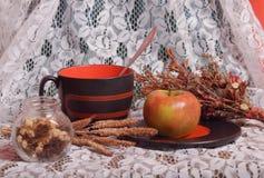Stillleben mit großem Becher, Apfel und getrockneten Kräutern Stockfoto