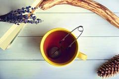 Stillleben mit großer gelber Tasse Tee Stockfotografie
