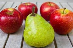Stillleben mit großer grüner Birne und roten Äpfeln stockfoto