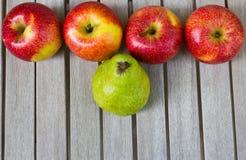 Stillleben mit großer grüner Birne und roten Äpfeln lizenzfreie stockfotografie