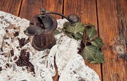 Stillleben mit hölzerner Kaffeemühle, Kaffeebohnen und Efeu auf einem alten Holztisch stockfotos