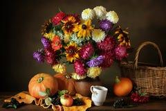 Stillleben mit Herbstblumen und -kürbisen Lizenzfreie Stockfotos
