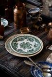 Stillleben mit intage Platten mit grünen Blumenverzierungen stehen auf rustikaler grauer Tabelle stockfoto
