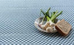 Stillleben mit jungem Knoblauch auf Weinleseplatte mit einem Frieden des Weißbrots, Nahaufnahme lizenzfreies stockfoto
