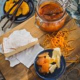 Stillleben mit Käse, Confiture und kandierter Orange auf dem rustikalen hölzernen Brett Lizenzfreies Stockbild