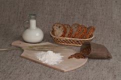 Stillleben mit Körnern des Weizens, der Spitzen, des Brotes, des Mehls und der Milch Lizenzfreie Stockfotos