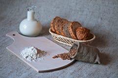 Stillleben mit Körnern des Weizens, des Brotes, des Mehls und der Milch Lizenzfreies Stockfoto