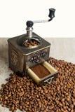 Stillleben mit Kaffeebohnen und alter Kaffeemühle auf dem hölzernen Hintergrund Stockbilder