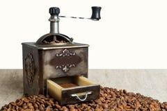 Stillleben mit Kaffeebohnen und alter Kaffeemühle auf dem hölzernen Hintergrund Lizenzfreies Stockfoto
