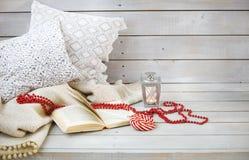 Stillleben mit Laterne, Süßigkeit, Buch und roten Perlen Stockfotos