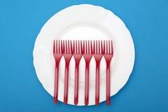 Stillleben mit Plastikgabeln und einer Platte auf einem blauen Hintergrund Stockfoto
