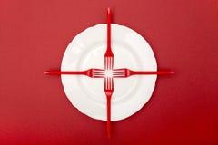 Stillleben mit Plastikgabeln und einer Platte auf einem roten Hintergrund Lizenzfreie Stockbilder