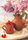 Stillleben mit süßer Kirsche und einem Blumenstrauß der Flieder Lizenzfreie Stockfotografie
