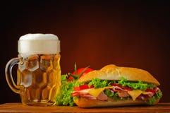 Stillleben mit Sandwich und Bier Lizenzfreies Stockfoto