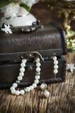 Stillleben mit Schatztruhe- und Perlenhalsketten Stockbild