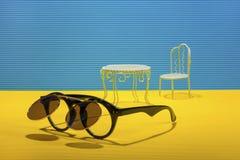 Stillleben mit Sonnenbrille, Tabelle und Stuhl auf einem gelb-blauen Hintergrund Lizenzfreie Stockbilder