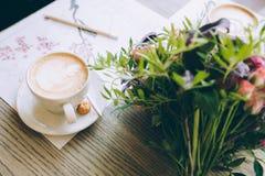 Stillleben mit Tasse Kaffee und Blumen Stockbild