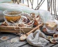 Stillleben mit transparenter Tasse Tee auf hölzernem Hintergrund Stockfoto