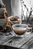 Stillleben mit transparenter Tasse Tee auf hölzernem Hintergrund Stockbilder