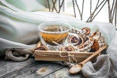 Stillleben mit transparenter Tasse Tee auf hölzernem Hintergrund Lizenzfreie Stockfotografie
