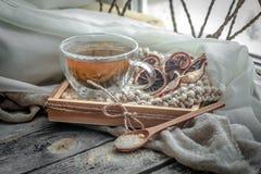 Stillleben mit transparenter Tasse Tee auf hölzernem Hintergrund Lizenzfreies Stockbild