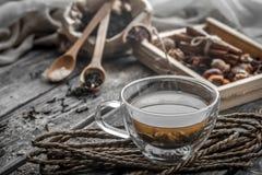 Stillleben mit transparenter Tasse Tee auf hölzernem Hintergrund Lizenzfreie Stockfotos