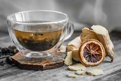 Stillleben mit transparenter Tasse Tee auf hölzernem Hintergrund Stockfotos
