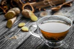 Stillleben mit transparenter Tasse Tee auf hölzernem Hintergrund Stockfotografie