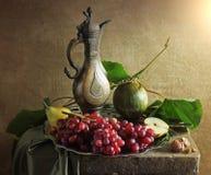 Stillleben mit Trauben und altem Krug Stockbild