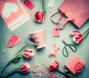 Stillleben mit Tulpen, rosa Schalen-, Einkaufstasche-, Geschenkbox-, Scher- und Papierumschlag mit Herzen, Draufsicht, flaches La Lizenzfreies Stockfoto