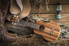 Stillleben mit Ukulele auf Cowboyhut und traditionellem Leder BO stockfotos