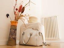 Stillleben mit Vase, Handtasche, Puff und Heizung Stockfotografie