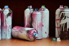 Stillleben mit vielen benutzten bunten Spraydosen Aerosolfarbe liegend auf der behandelten Holzoberfläche im Künstler ` s Stockbilder