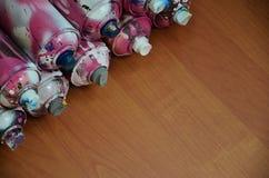 Stillleben mit vielen benutzten bunten Spraydosen Aerosolfarbe liegend auf der behandelten Holzoberfläche im Künstler ` s Lizenzfreie Stockfotografie