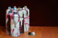 Stillleben mit vielen benutzten bunten Spraydosen Aerosolfarbe liegend auf der behandelten Holzoberfläche im Künstler ` s Lizenzfreie Stockfotos