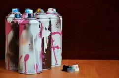 Stillleben mit vielen benutzten bunten Spraydosen Aerosolfarbe liegend auf der behandelten Holzoberfläche im Künstler ` s Lizenzfreies Stockfoto
