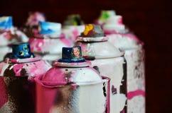 Stillleben mit vielen benutzten bunten Spraydosen Aerosolfarbe liegend auf der behandelten Holzoberfläche im Künstler ` s Stockfotos