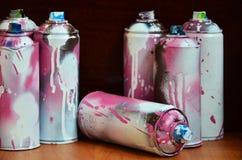 Stillleben mit vielen benutzten bunten Spraydosen Aerosolfarbe liegend auf der behandelten Holzoberfläche im Künstler ` s Stockfoto