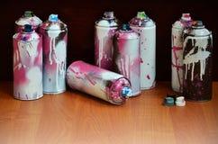 Stillleben mit vielen benutzten bunten Spraydosen Aerosolfarbe liegend auf der behandelten Holzoberfläche im Künstler ` s g Lizenzfreies Stockfoto