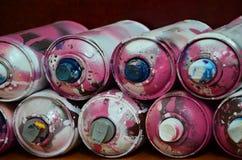 Stillleben mit vielen benutzten bunten Spraydosen Aerosolfarbe liegend auf der behandelten Holzoberfläche im Künstler ` s g Stockbilder
