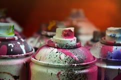 Stillleben mit vielen benutzten bunten Spraydosen Aerosolfarbe liegend auf der behandelten Holzoberfläche im Künstler ` s g Lizenzfreie Stockfotografie