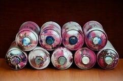Stillleben mit vielen benutzten bunten Spraydosen Aerosolfarbe liegend auf der behandelten Holzoberfläche im Künstler ` s g Lizenzfreies Stockbild
