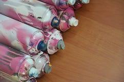 Stillleben mit vielen benutzten bunten Spraydosen Aerosolfarbe liegend auf der behandelten Holzoberfläche im Künstler ` s g Stockbild