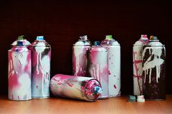 Stillleben mit vielen benutzten bunten Spraydosen Aerosolfarbe liegend auf der behandelten Holzoberfläche im Künstler ` s g Stockfotos