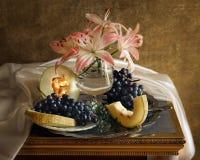 Stillleben mit weißer Lilie, Trauben und Melone Lizenzfreies Stockfoto