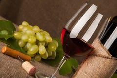 Stillleben mit Weinflaschen, -gläsern und -trauben Stockfotografie