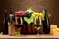 Stillleben mit Weinflaschen, -gläsern und -trauben Stockbilder