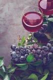 Stillleben mit Weingläsern, Flaschen, Trauben und Blättern Lizenzfreies Stockbild